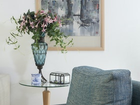 אגרטל כחול עם פרחים ורודים וכורסת בד אפורה