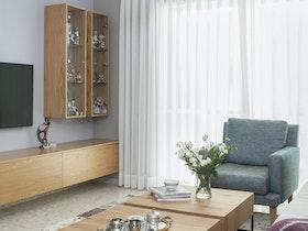 שני שולחנות מרובעים מעץ זה לצד זה בסלון