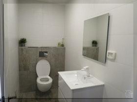 שירותים משופצים עם כיור לבן וברז ניקל