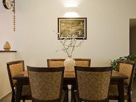 פינת אוכל חומה עם 6 כסאות ואגרטל לבן