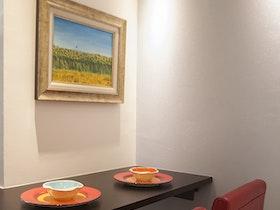 2 כסאות בר אדומות עם תמונה קטנה על הקיר