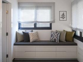 תכנון ועיצוב ספסל ישיבה, המשמש גם לאחסון, ביחידת ההורים.