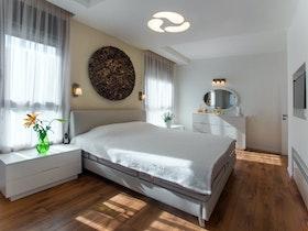 מיטה זוגית אפורה עם קומודה לבנה ומגירות