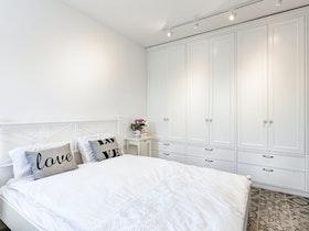 חדר שינה לאחר שיפוץ עם ארונות בגדים לבנים
