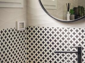 חדר אמבטיה עם מראה כסופה עגולה וכיור שחור