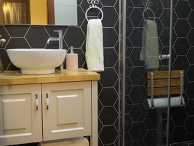 מקלחון זכוכית שקוםה עם כיור לבן ליד