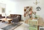 חלל סלון עם ספות ישיבה, שולחן סלון, ארון כוורת ופינת אוכל