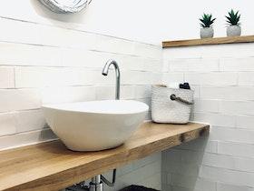 חדר שירותים מעוצב עם שירותים צפים, מראה כסופה עגולה וכיור לבן