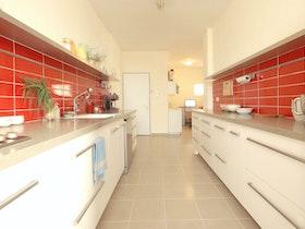מטבח עם קרמיקה אדומה ואורנות לבנים