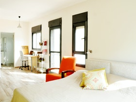מיטה זוגית עם מזרן וכריות בחדר מואר ומשופץ