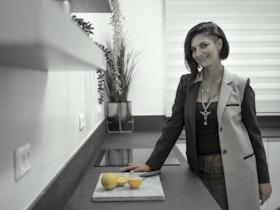 גברת במטבח משופץ עם 2  מדפים תלויים