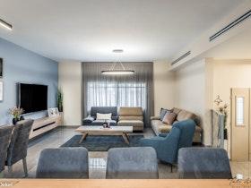 תמונת זום אאוט עם סלון מעוצב, טלוויזיה תלויה מעל מזנון צף, שולחנות אוכל ודלת כניסה