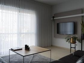 סלון מעוצב עם וילון גלי + טלויזיה תלוייה על הקיר