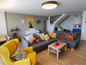 חלל סלון בבית פרטי עם שולחן סלון וכורסת ישיבה צהובה