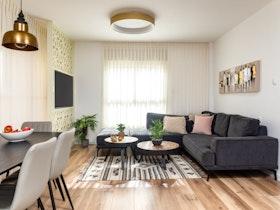 ספה פינתית עם 2 שולחנות עגולים וטלויזיה תלוייה