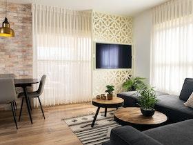 ספה פינתית עם 2 שולחנות וטלויזיה