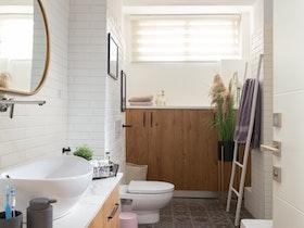 מקלחת משופצת עם ארונות בצבע אגס מוזהב