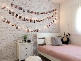 מיטה וחצי עץ לבן בחדר ילדים מעוצב ושידה ליד