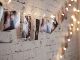קיר עם טפט לבנות עם פס מנורות דלוקות עטופות בתמונות