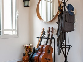 חדר מעוצב עם פרקט חום, עם מתלה בגדים וסטנד גיטרות