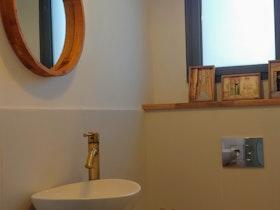 שירותים מעוצבים עם כיור לבן ומראה על הקיר