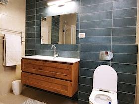 אמבטיה עם קרמיקה בצבע כחול וארונית חומה