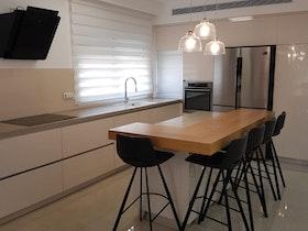 אי מטבח עם כסאות בר ומטבח חדש
