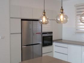 תמונה של מטבח משופץ עם גוף תאורה תלוי מהתקרה