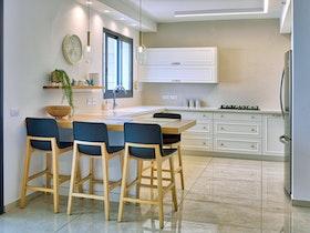 מטבח עם כסאות בר וריצוף לבן