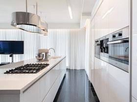 תמונה של מטבח לבן עם אי ארוך