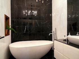 מקלחת מעוצבת עם קרמיקה שחורה ואמבט