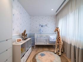 חדר ילדים עם מיטת תינוק וצעצוע ג'ירפה