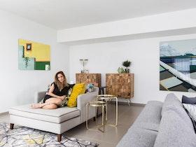 צילום של סלון עם אישה על הספה