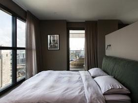 צילום של חדר שינה עם מיטה זוגית ירוקה ונוף לעיר