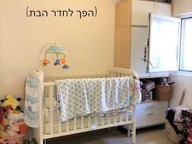 מיטת תינוק עם ארון אחסון ליד בחדר מואר