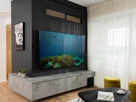 קיר מסוייד וצבוע בשחור עם טלויזיה גדולה תלוייה, מאוור תקרה בחלל מעוצב ומשופץ