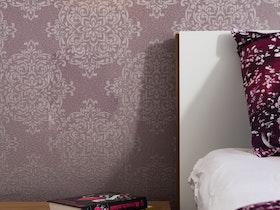 צילום שידת צד ליד מיטה זוגית עם טפט קיר סגול
