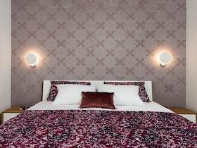 צילום חדר שינה זוגי עם מיטה זוגית וטפט סגול