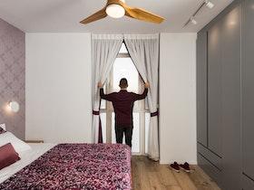 חדר הורים משופץ עם ארונות אפורים נסתרים