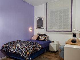 חדר ילדים עם מיטה וחצי וקיר סגול ומאוורר תקרה