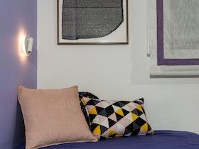חדר ילדים עם מיטה, כריות נוי ותמונה על הקיר