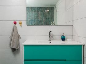מקלחת משופצת עם ארונית בצבע טורקיז
