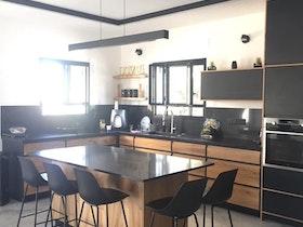 מטבח עם שיש שחור וארונות מטבח שחורים