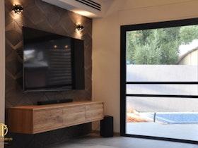 בית פרטי עם סלו שיש בו מזנון צף וטלויזיה תלוייה על הקיר