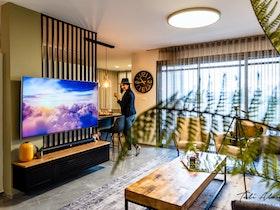 סלון יוקרתי עם טלויויזיה מסך גדולה, שעון קיר, אישה עם כובע חום בתמונה.