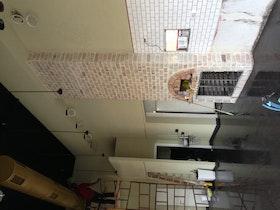 חיפוי אבני סיליקט מעל לטאבון ובריקים לבנים בקירות